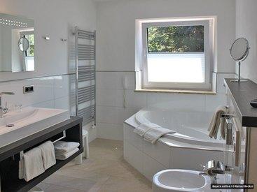 ...großzügigem Bad mit Whirlpool-Badewanne und Dusche