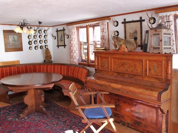 Sitzecke und Klavier in der Wohnstube der Murmeleshütte